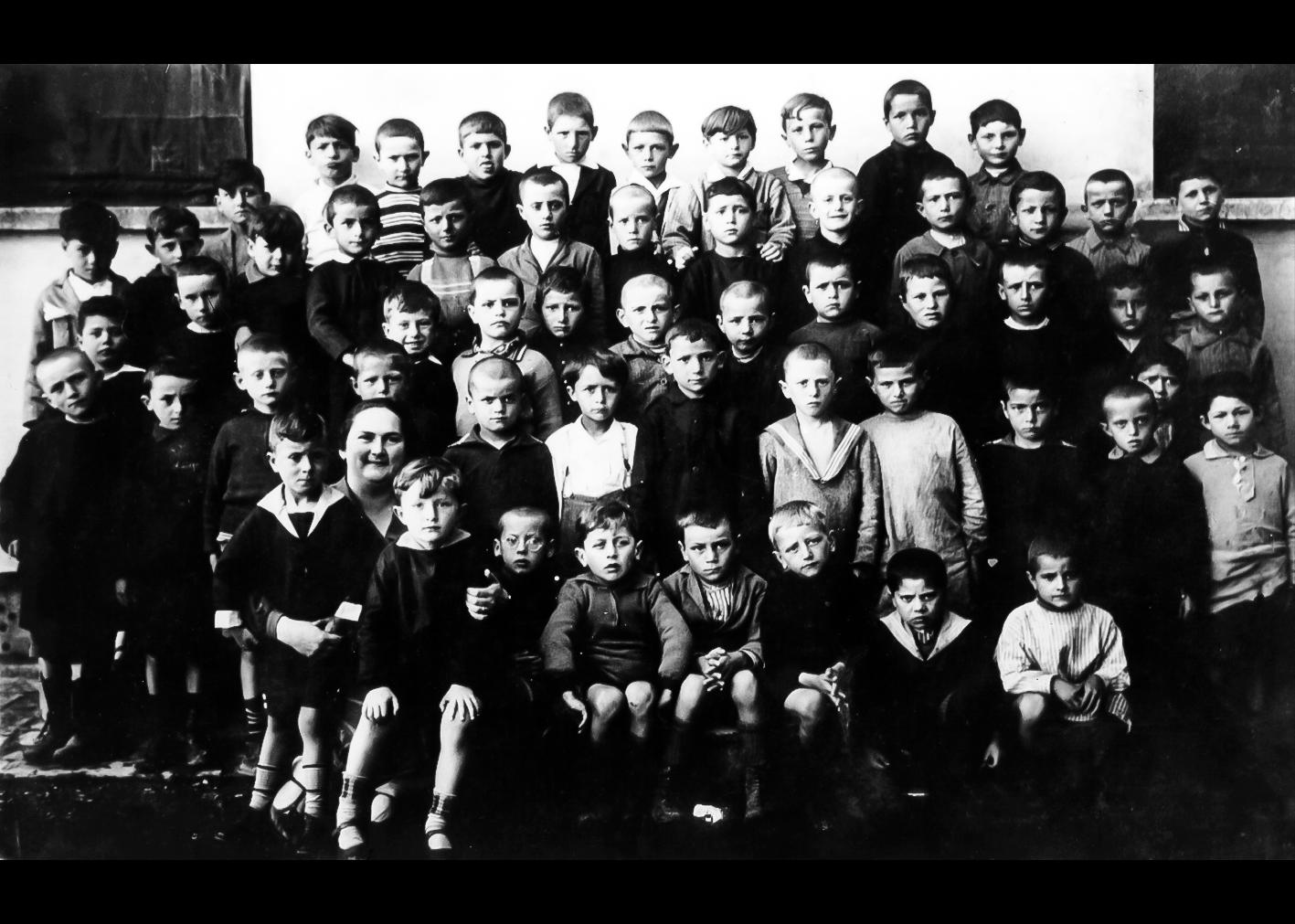 Una seconda elementare maschile del 1927-28. Da sinistra in prima fila in alto: Vaccari Gualtiero (un po' più in basso con la nuca appoggiata al davanzale della finestra), .........., .........., Baroni, Mario, Malservisi Marino, Govoni Luciano, Ansaloni Ugo, Schiavina Nario, ........, Orsini Elio. Da sinistra in seconda fila: .........., Lodi Augusto, Bettoli Bruno, Corazza Duilio, Mazza Radames, ..........., ............, .........., Lodi Fernando, Malaguti Luigi, Toselli Luigi, Zanotti Ugo, .......... Terza fila da sinistra: Gardini Fulvio, Atti Dante, Bergonzoni Adriano, Chiossi Enzo, ..........., Bovina Alessandro, Orsini Ido, ............, Rimondi Timoteo, Bergamini Dealmo, ..........., Ansaloni Ugo. Quarta fila da sinistra: Bonazzi Arrigo, Manferdini Aldo, Cremonini Donino, Guidi Odolone, Cremonini Lodovico, Paltrinieri Bruno, Scaramagli Amedeo, Toselli Pietro, Preti Giuseppe, ............, ............, Manferdini Mario (seminascosto), Tassi Arrigo. Quarta fila da sinistra: ............, la maestra Tura Jolanda, Lambertini Bruno, Pedriali Arrigo, ............, Tassinari Osvaldo, Cremonini Donino, ........., Fini Mario.